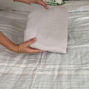 hands holding folded sheet over bed
