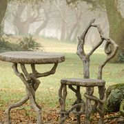 an image of a faux bois chair and table set amongst trees on a misty day