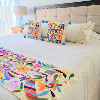 a bedroom designed by soluna paz features otomi embroidery on a blanket and a pair of pillows