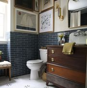 nautical bathroom, blue subway tile, framed pictures, wooden console