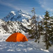 orange 4 season tent pitched in snowy mountains