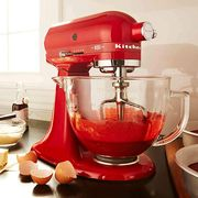red colored kitchenaid stand mixer sitting on counter with baking supplies