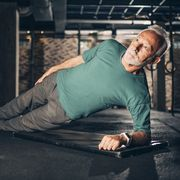 active, sporty elderly athlete doing a sideways plank exercise in a gym