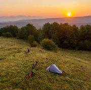 adventure concept image with couple watching a beautiful sunset on a mountain with their tent and mountain bikes aside