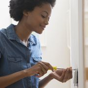 african american woman fixing light switch