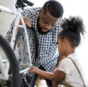 african father and daughter are fixed a bicycle together adjusting tightening a bicycle wheel at home