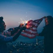 Afro amercian man and woman celebrating with USA flag and