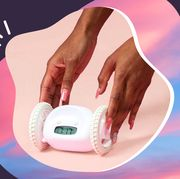 woman with pink nails holding clocky wheeled alarm clock with sunrise background