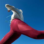 woman jumping in red leggings against blue sky