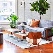 small living room and dining room, gray couch, black floor lamp plants, coffee table, round white dining table, black chairs