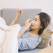 an asian chinese female lying on sofa looking at the thermometer with her pajamas and blanket