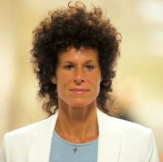 andrea constand in a white suit jacket walking through the courtroom