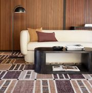 brown and mauve rug under a sofa
