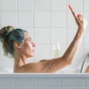 woman in bathtub taking a selfie with champagne