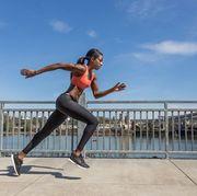 Attractive ethnic female sprinter training in the city