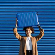 woman holding blue away luggage above head