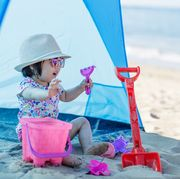 baby on beach sitting in front of a tent