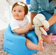 baby sitting in a blue bumbofloor seat on plush shag rug with mother handing baby rabbit stuffed animal