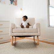 baby sitting on glider in nursery