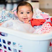 baby sitting in laundry basket