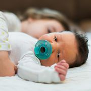sister hugging infant with pacifier