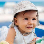 baby wearing sun hat lounging on beach