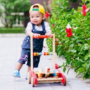 toddler babyboy in denim overalls walking withcolorful walking toy outdoors by flowers