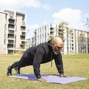 bald man doing push ups on exercise mat at park