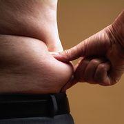 bare chested senior man pinching skin around waist mid section