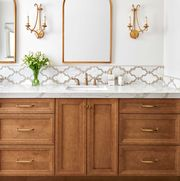 bathroom, white walls, brown cabinets, white marble countertops, gold sconces and gold mirror