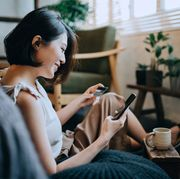 beautiful smiling young asian woman chilling at home, sitting on the floor in bedroom, enjoying a cup of coffee and shopping online with smartphone while making mobile payment with credit card on hand