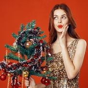 Beautiful woman in a Christmas dress with a Christmas tree in her hands