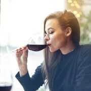 beautiful young woman drinking red wine with friends in cafe, portrait with wine glass near window vocation holidays evening concept
