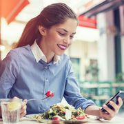 beautiful young woman using an application to send an sms message in her smartphone device while eating a salad