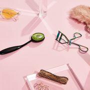 perfume, sunglasses, crystal, sleep mask, eyelash curler and jewelry on pink background