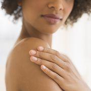 beauty shot of woman touching shoulder, studio shot
