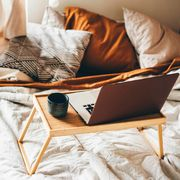 laptop and mug on wooden tray in bed