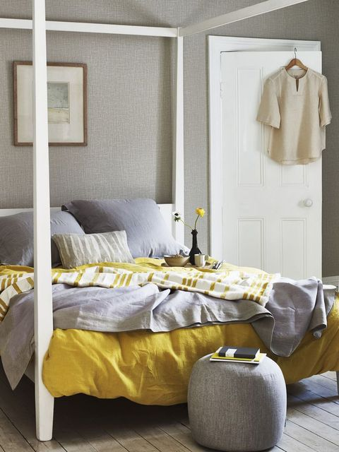 feng shui bedroom, bedroom with white modern four poster bed, grey and mustard yellow bed linen