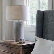 cement bedroom lamp next to grey bed