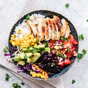 The best breastfeeding diet includes foods such as vegetables, fruits, and lean proteins like those that are featured in this grilled chicken burrito bowl