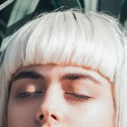 woman with bleached blonde hair and dark eyebrows with eyes closed
