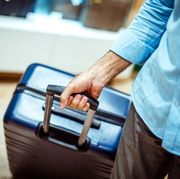 big navy blue travel suitcase being held by an unrecognizable person in a bags and accessories store