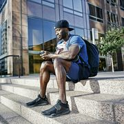 black man sitting on city staircase texting on cell phone