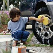 boy washing car wheel with sponge