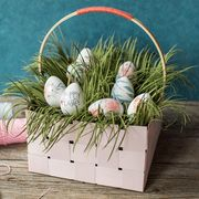 basket with eggs and grass and a bunny made of popsicle sticks