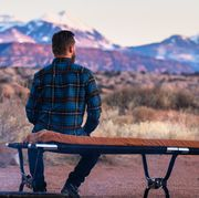 man wearing plaid flannel shirt sitting on camping cot by fire in desert looking at mountains