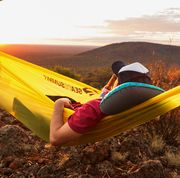 man drinking a beer in a hammock at sunset lying on teal and black camping pillow