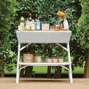 white bar cart in hedges