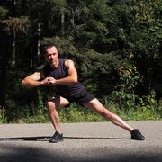 caucasian male runner athlete stretching outdoors in forest