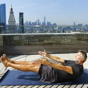caucasian man practicing yoga on urban rooftop